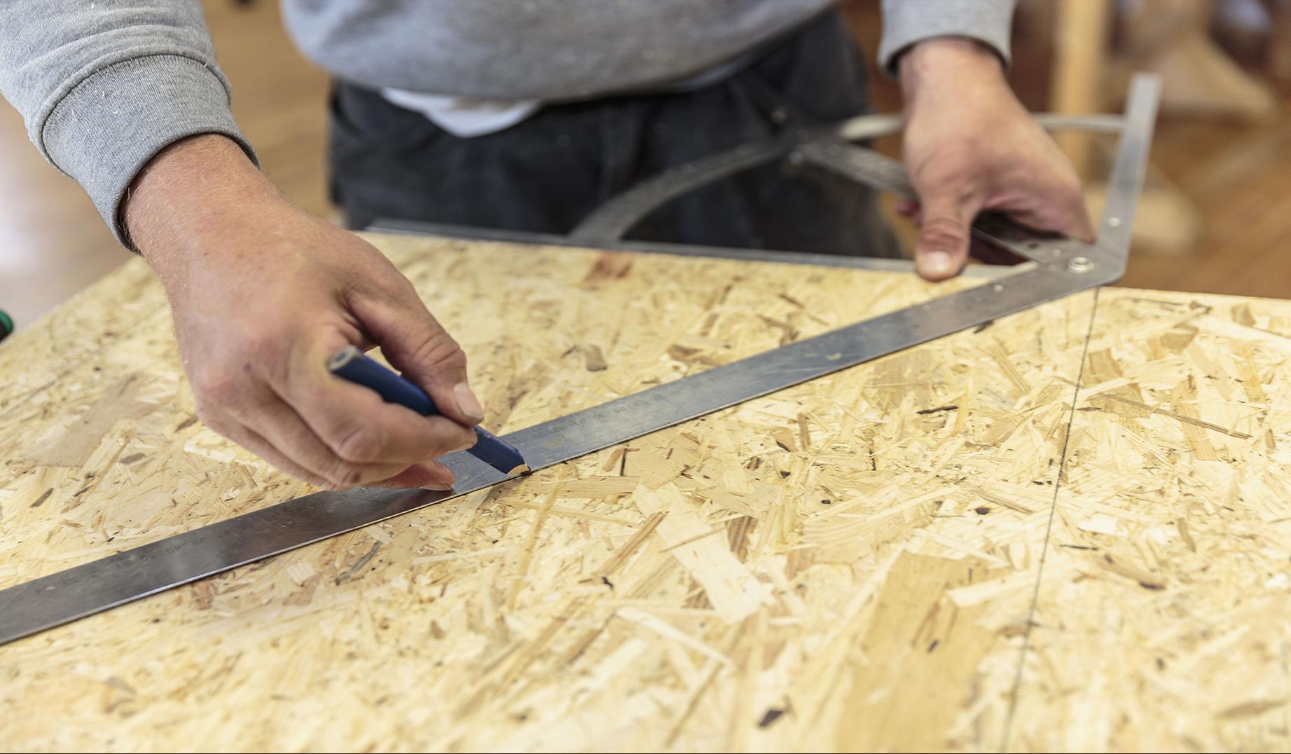 Mann zeichnet Markierungen auf eine Holzplatte